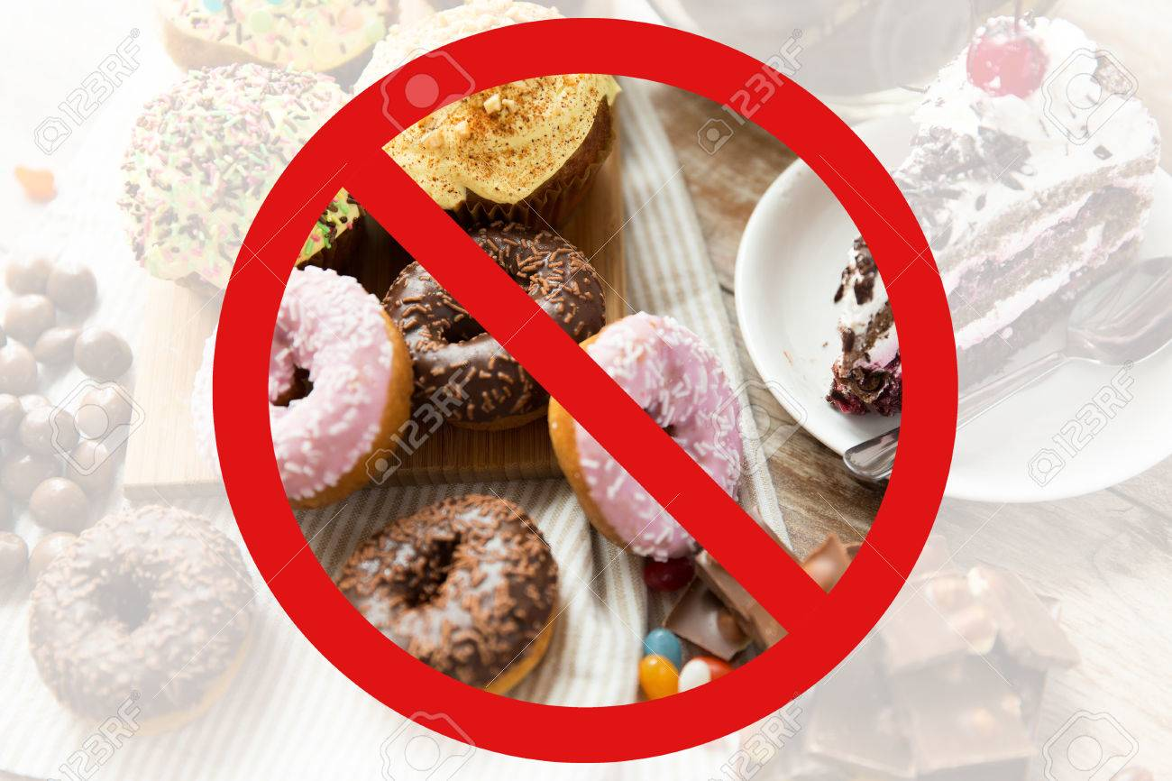 fast food, low carb diet, fattening and unhealthy eating concept - close up of glazed donuts, cakes and chocolate sweets behind no symbol or circle-backslash prohibition sign - 52917092