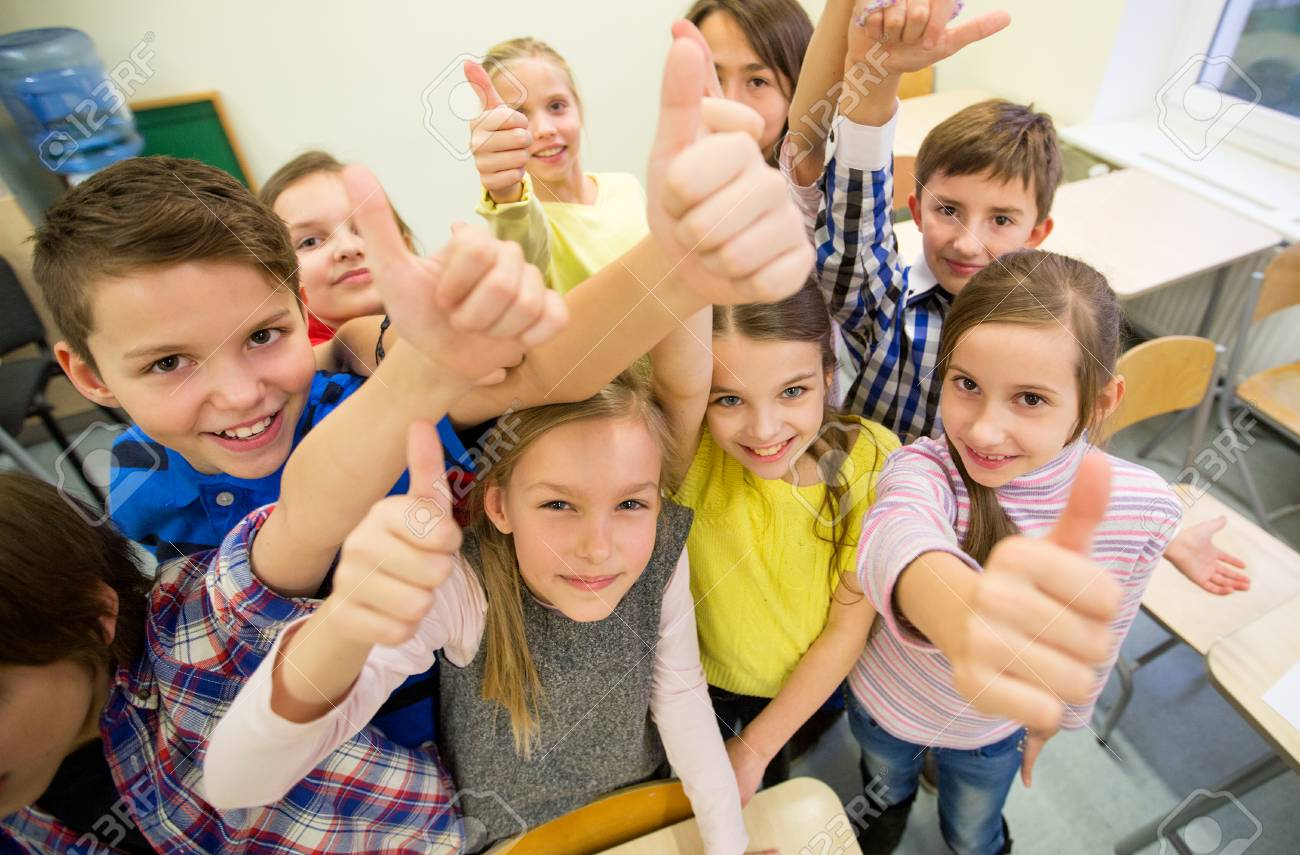 education, elementary school, learning, gesture and people concept - group of school kids and showing thumbs up in classroom - 53107502