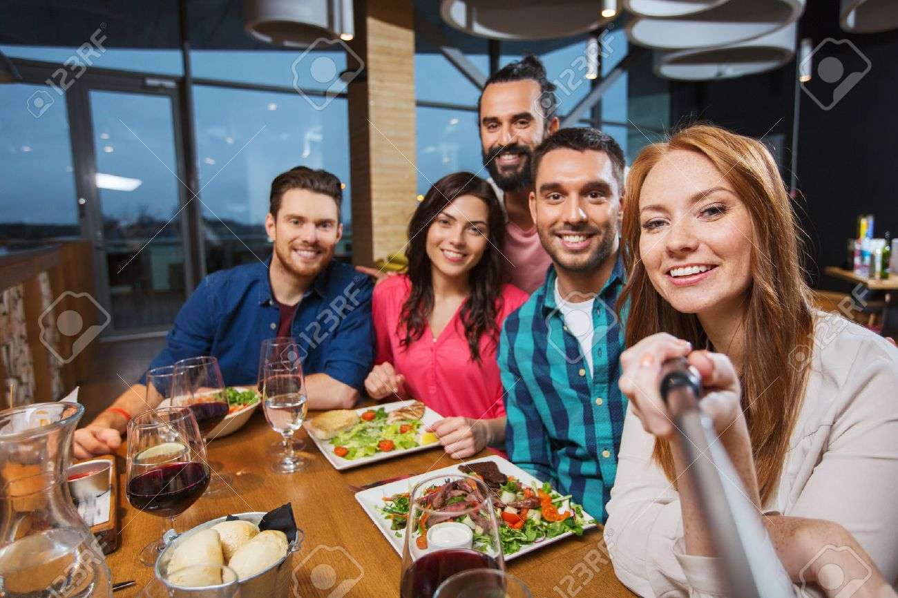 leisure, technology, friendship, people and holidays concept - happy friends having dinner and taking picture by selfie stick at restaurant - 53241227