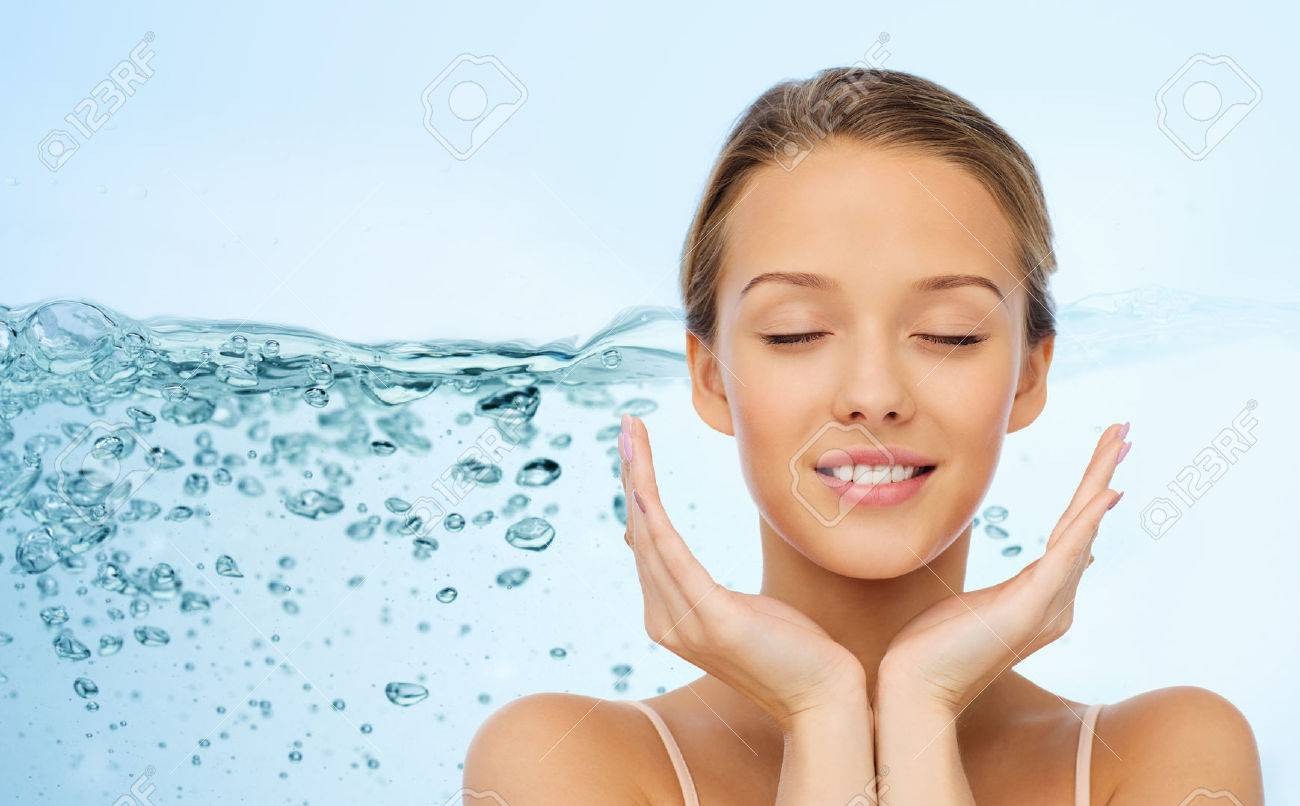 beauty, people, skincare and health concept - smiling young woman face and hands over water splash on blue background - 53315896