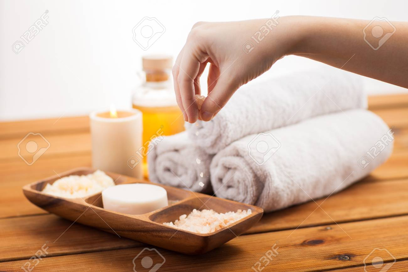 beauty, spa, body care and natural cosmetics concept - close up of hand pouring himalayan salt in wooden bowl with soap, scrub and bath towels on table - 53475519