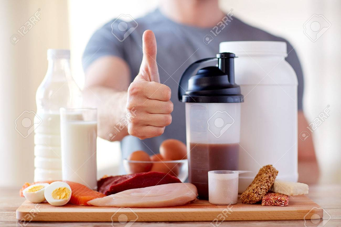 sport, fitness, healthy lifestyle, diet and people concept - close up of man with food rich in protein showing thumbs up - 53578416