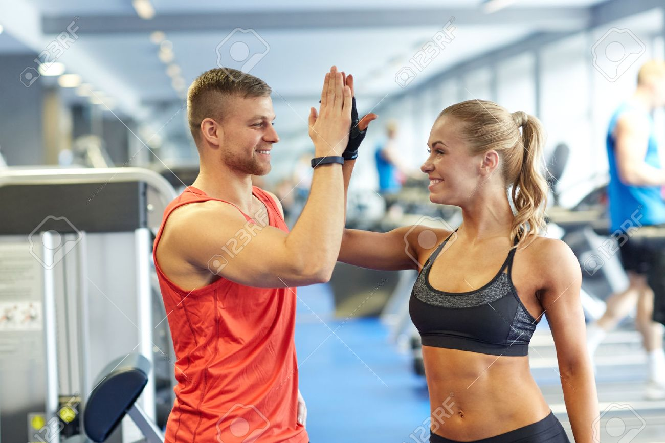sport, fitness, lifestyle, gesture and people concept - smiling man and woman doing high five in gym - 54750894