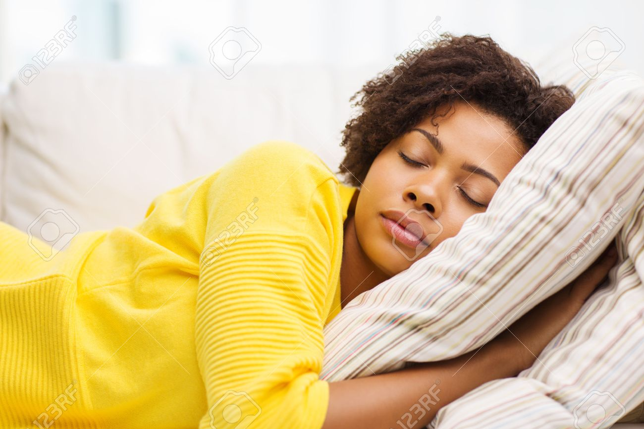 people, rest, comfort and leisure concept - african american young woman sleeping on sofa at home - 53856905