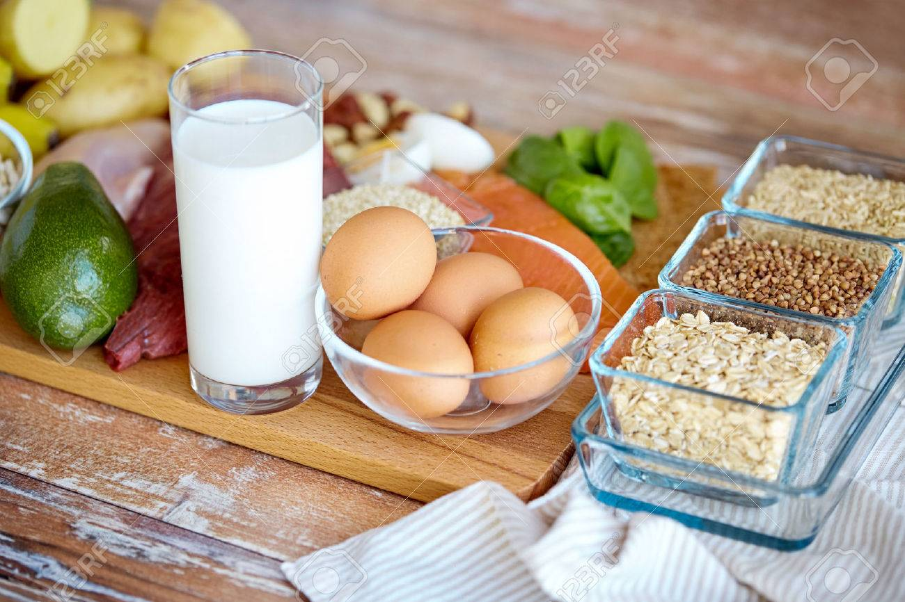 balanced diet, cooking, culinary and food concept - close up of eggs, cereals and milk glass on wooden table - 53927722