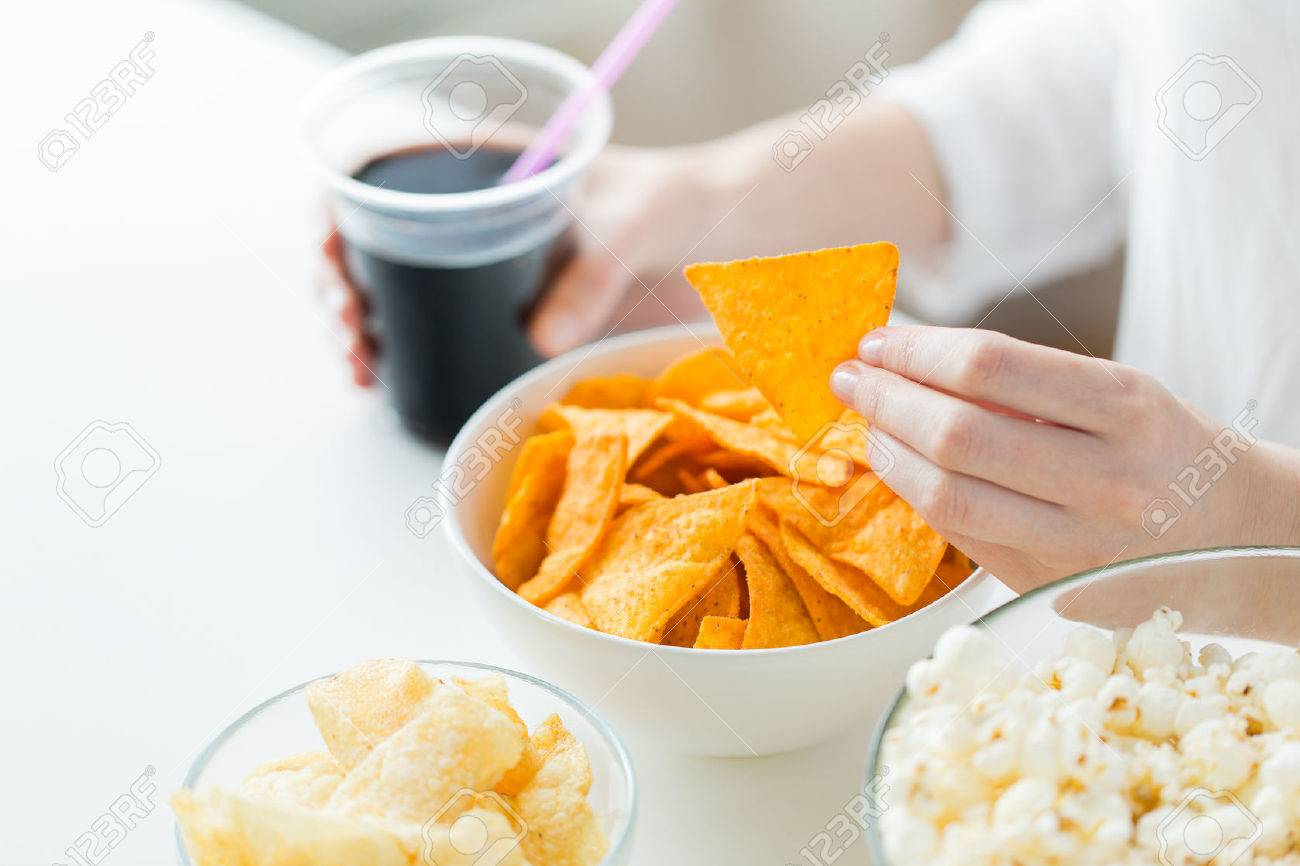 people, fast food, junk-food and unhealthy eating concept - close up of woman with popcorn, nachos or corn crisps and peanuts in bowls Stock Photo - 53928641