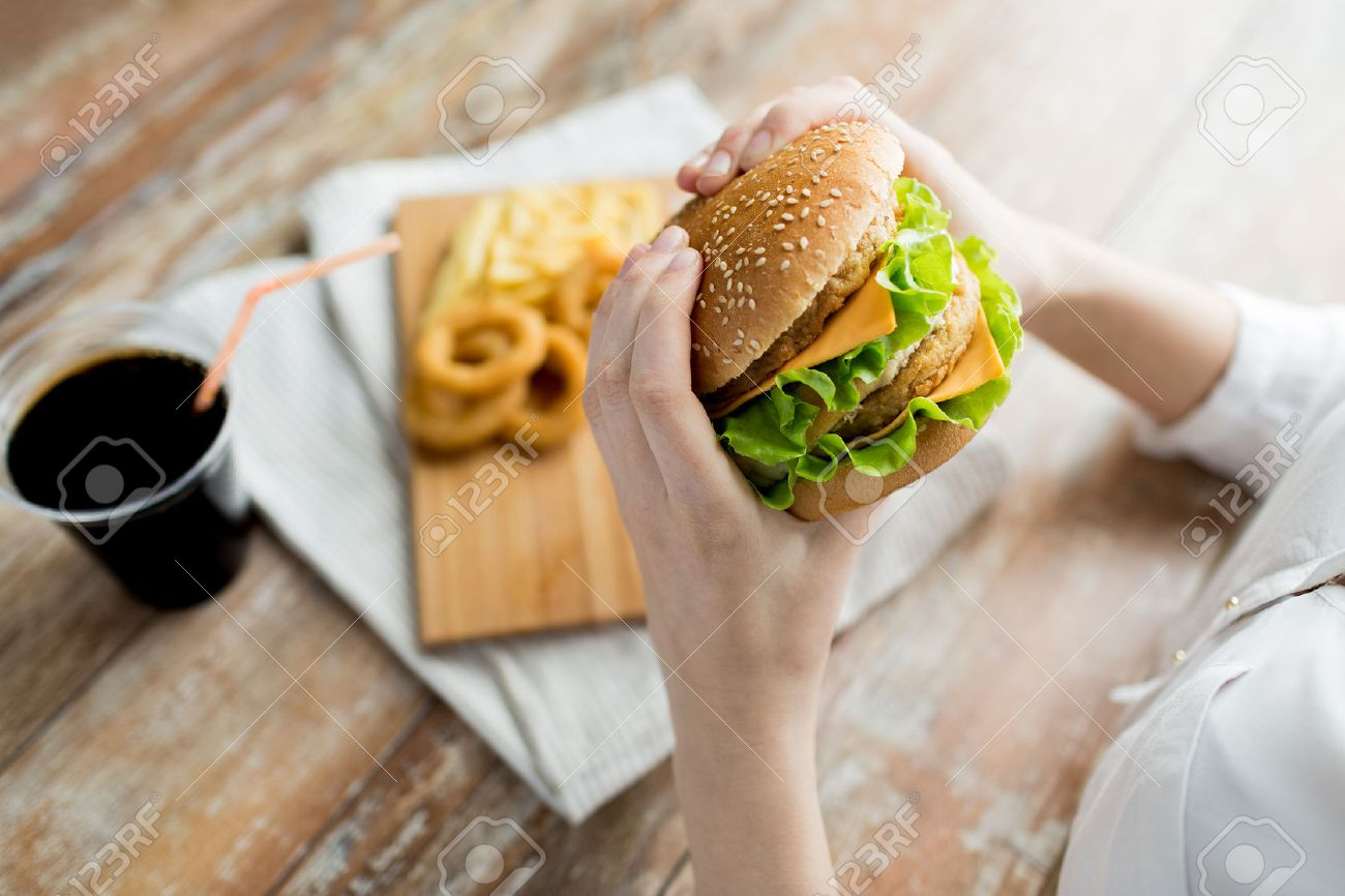 fast food, people and unhealthy eating concept - close up of woman hands holding hamburger or cheeseburger Stock Photo - 55283526