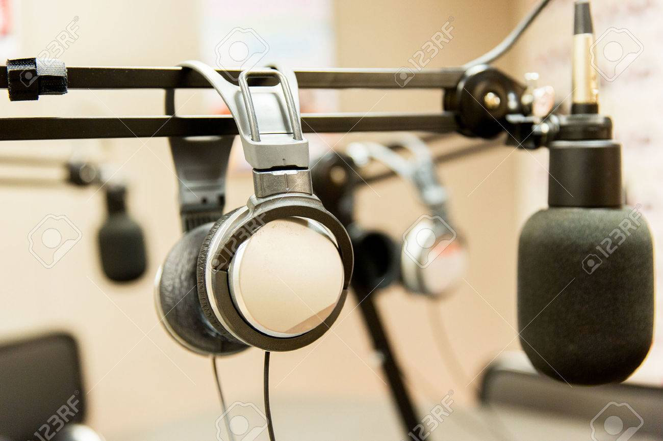 technology, electronics and audio equipment concept - close up of headphones and microphone at recording studio or radio station - 53971309