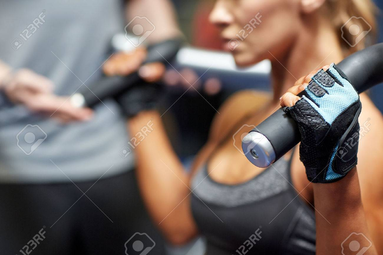 sport, fitness, bodybuilding, teamwork and people concept - young woman and personal trainer flexing muscles on gym machine - 54046259