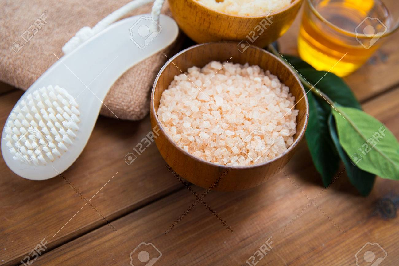 beauty, spa, body care, natural cosmetics and bath concept - close up of himalayan pink salt with brush on wooden table - 54056835