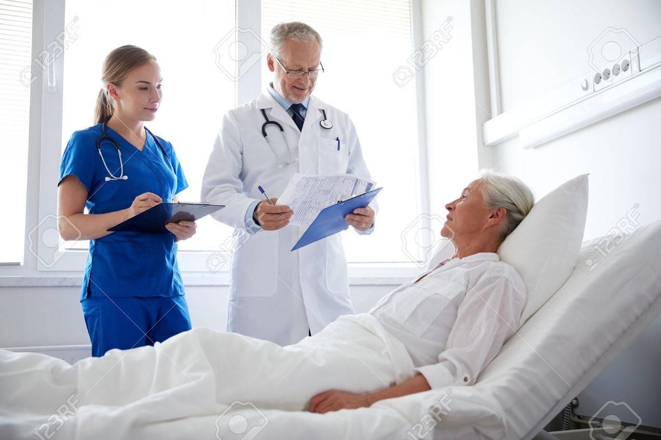 fafd9b689 Foto de archivo - La medicina, la edad, la salud y las personas concepto -  médico y la enfermera con sujetapapeles que visitan la mujer mayor paciente  en ...