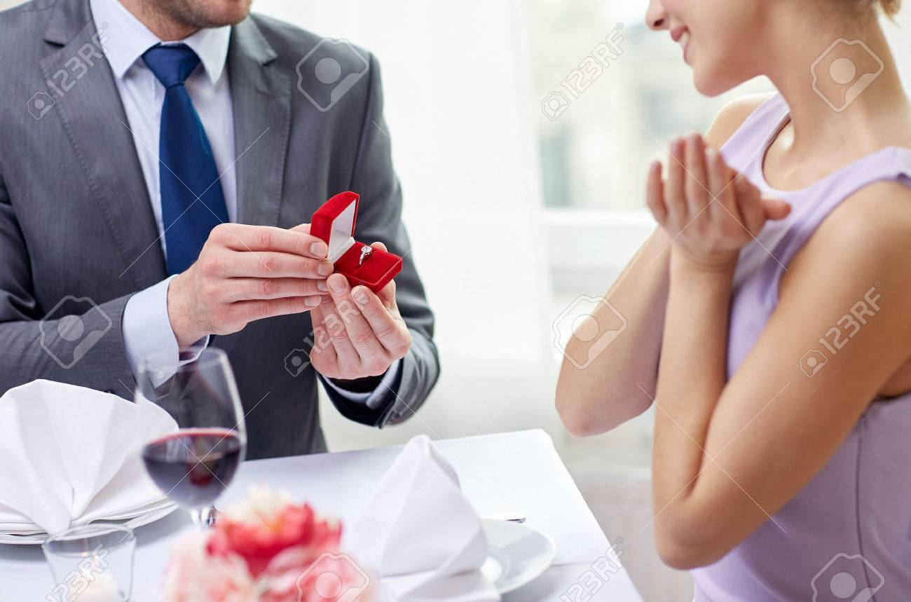 couple, love, engagement and holiday concept - close up of excited young woman and boyfriend giving her ring at restaurant - 54304567