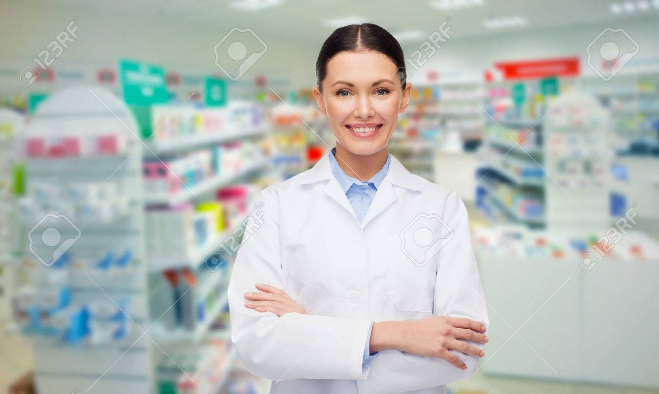 medicine, pharmacy, people, health care and pharmacology concept - happy young woman pharmacist over drugstore background - 54400025