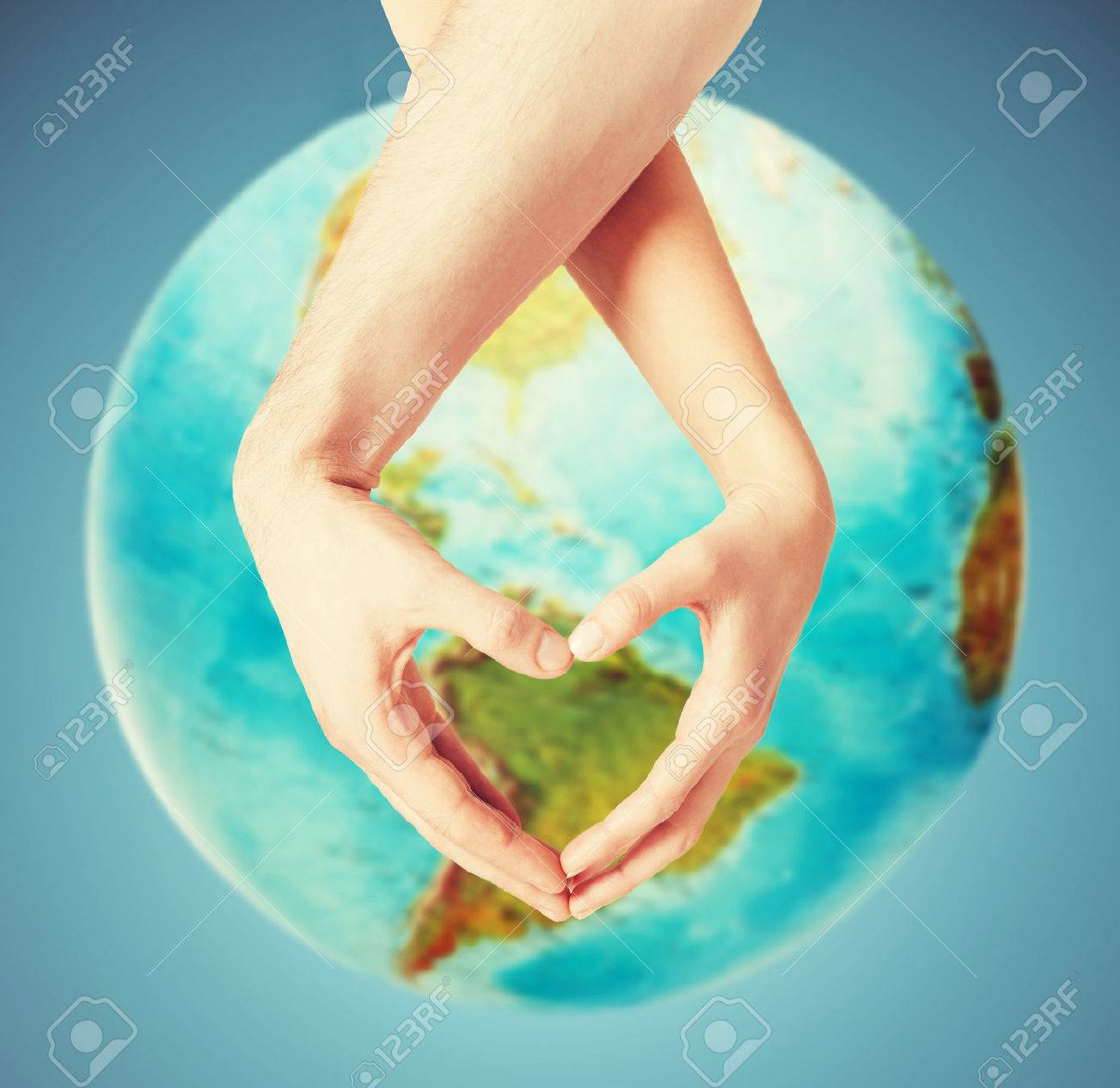 people, peace, love, life and environmental concept - close up of human hands showing heart shape gesture over earth globe and blue background - 54407059