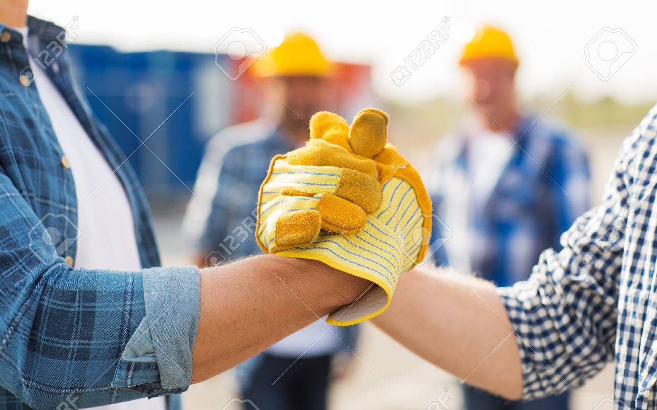 building, teamwork, partnership, gesture and people concept - close up of builders hands in gloves greeting each other with handshake on construction site - 54443933