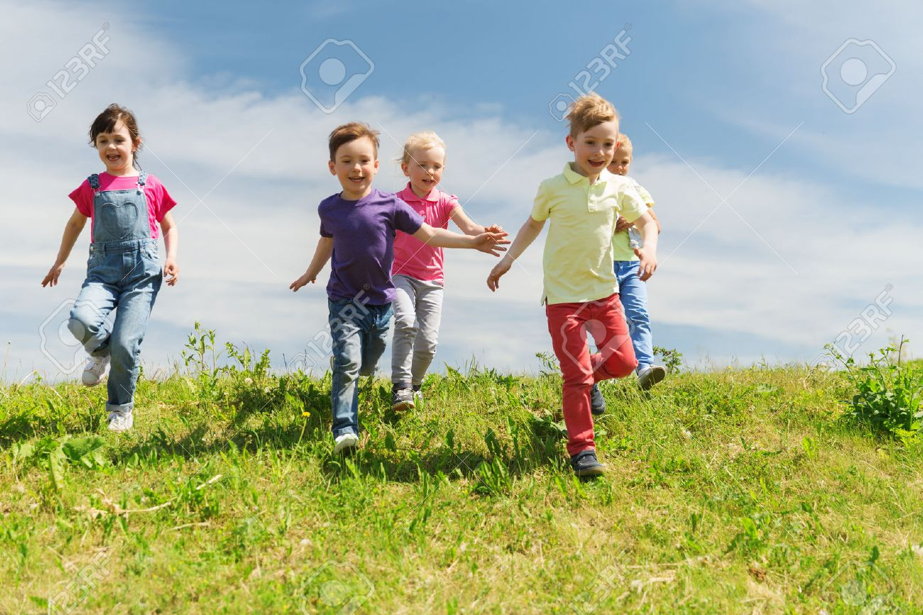 summer, childhood, leisure and people concept - group of happy kids playing tag game and running on green field outdoors - 54443941