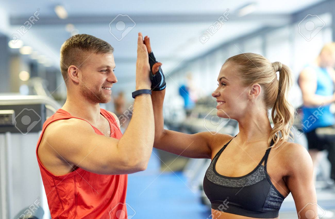 sport, fitness, lifestyle, gesture and people concept - smiling man and woman doing high five in gym - 54718015