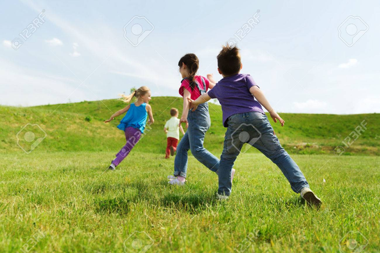 summer, childhood, leisure and people concept - group of happy kids playing tag game and running on green field outdoors - 54718073