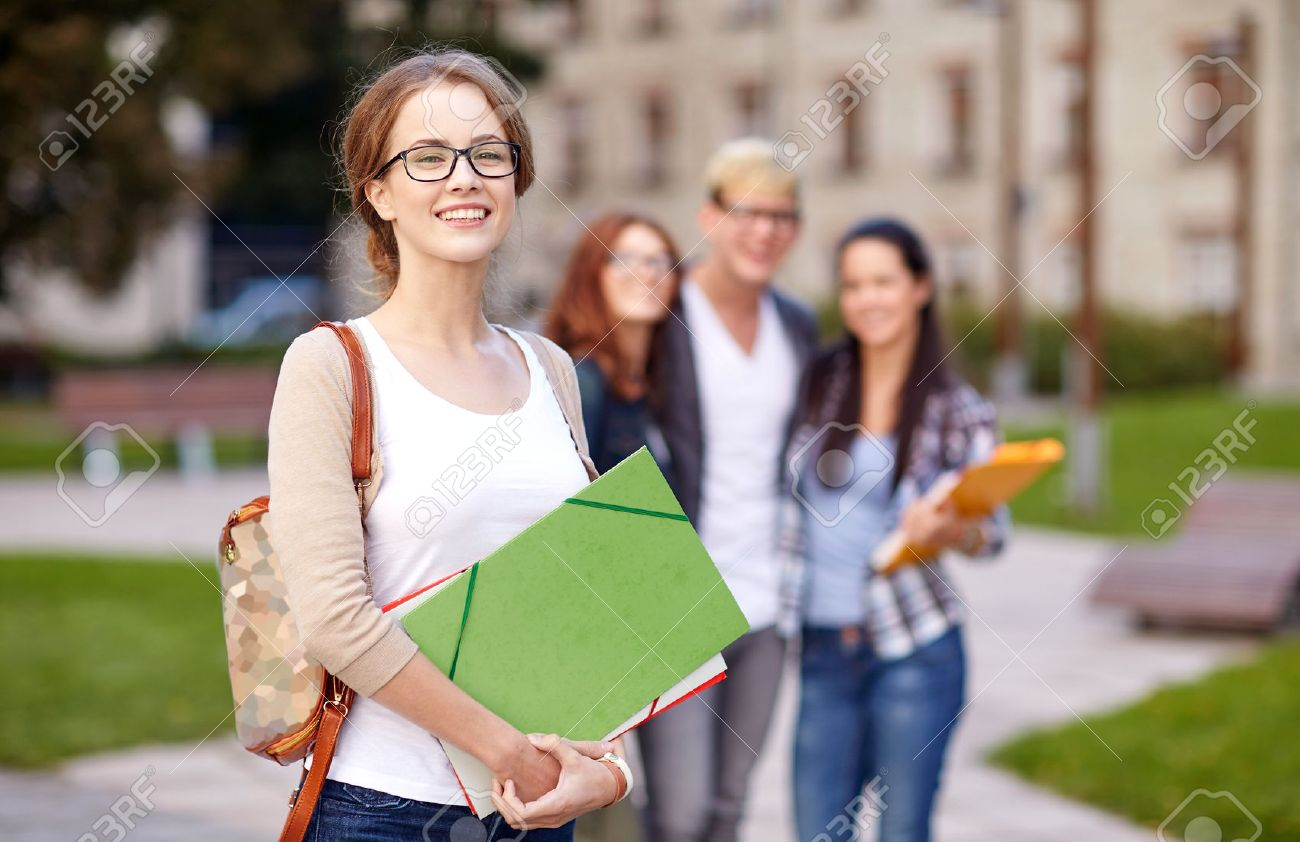 education, campus, friendship and people concept - group of happy teenage students with school folders - 54720397