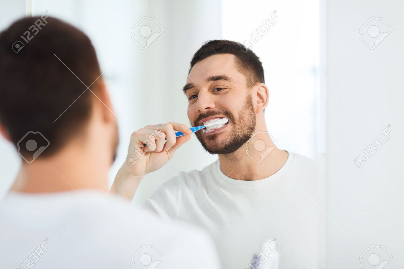 health care, dental hygiene, people and beauty concept - smiling young man with toothbrush cleaning teeth and looking to mirror at home bathroom - 54867700