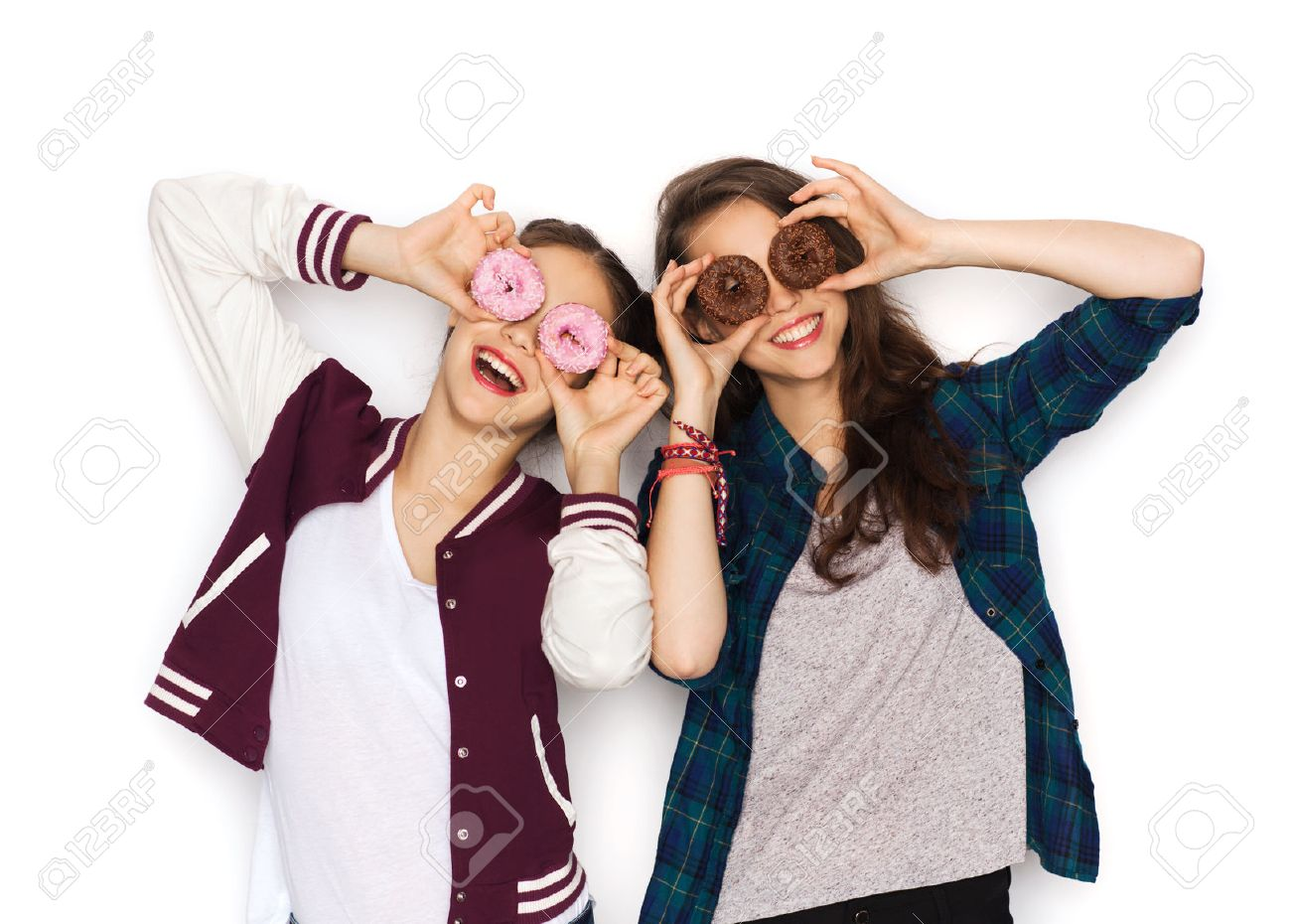 people, friends, teens and friendship concept - happy smiling pretty teenage girls with donuts making faces and having fun - 54864220