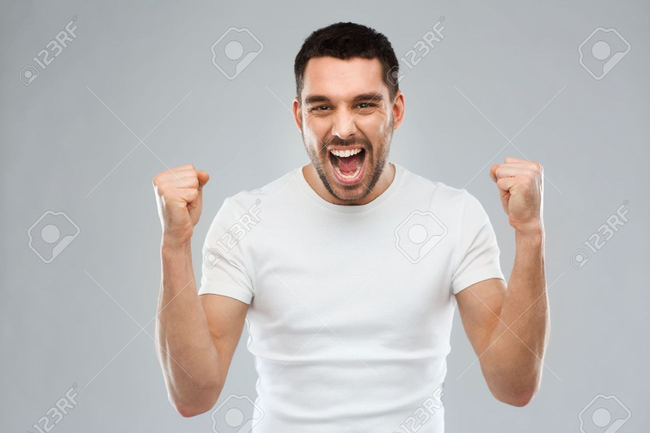 emotion, success, gesture and people concept - young man celebrating victory over gray background - 54859663