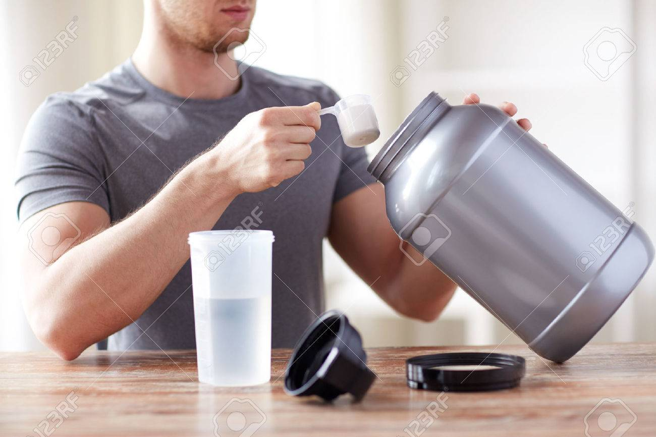 sport, fitness, healthy lifestyle and people concept - close up of man with jar and bottle preparing protein shake - 54776175