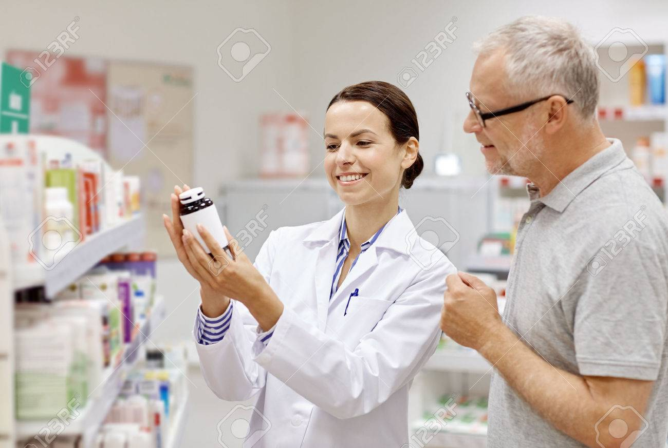 medicine, pharmaceutics, health care and people concept - happy pharmacist showing drug to senior man customer at drugstore - 54776679