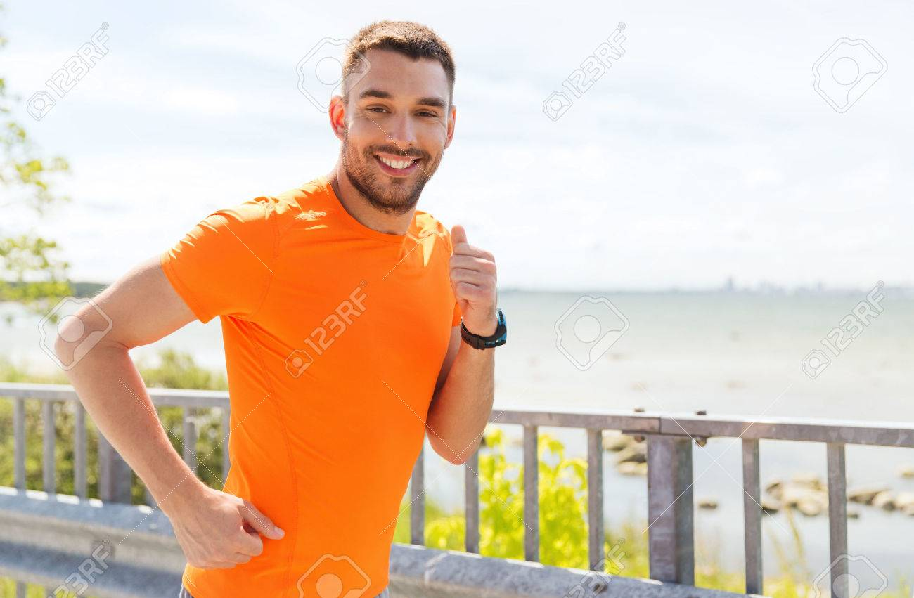 fitness, sport, people, technology and healthy lifestyle concept - smiling young man with heart rate watch running at summer seaside - 54776693