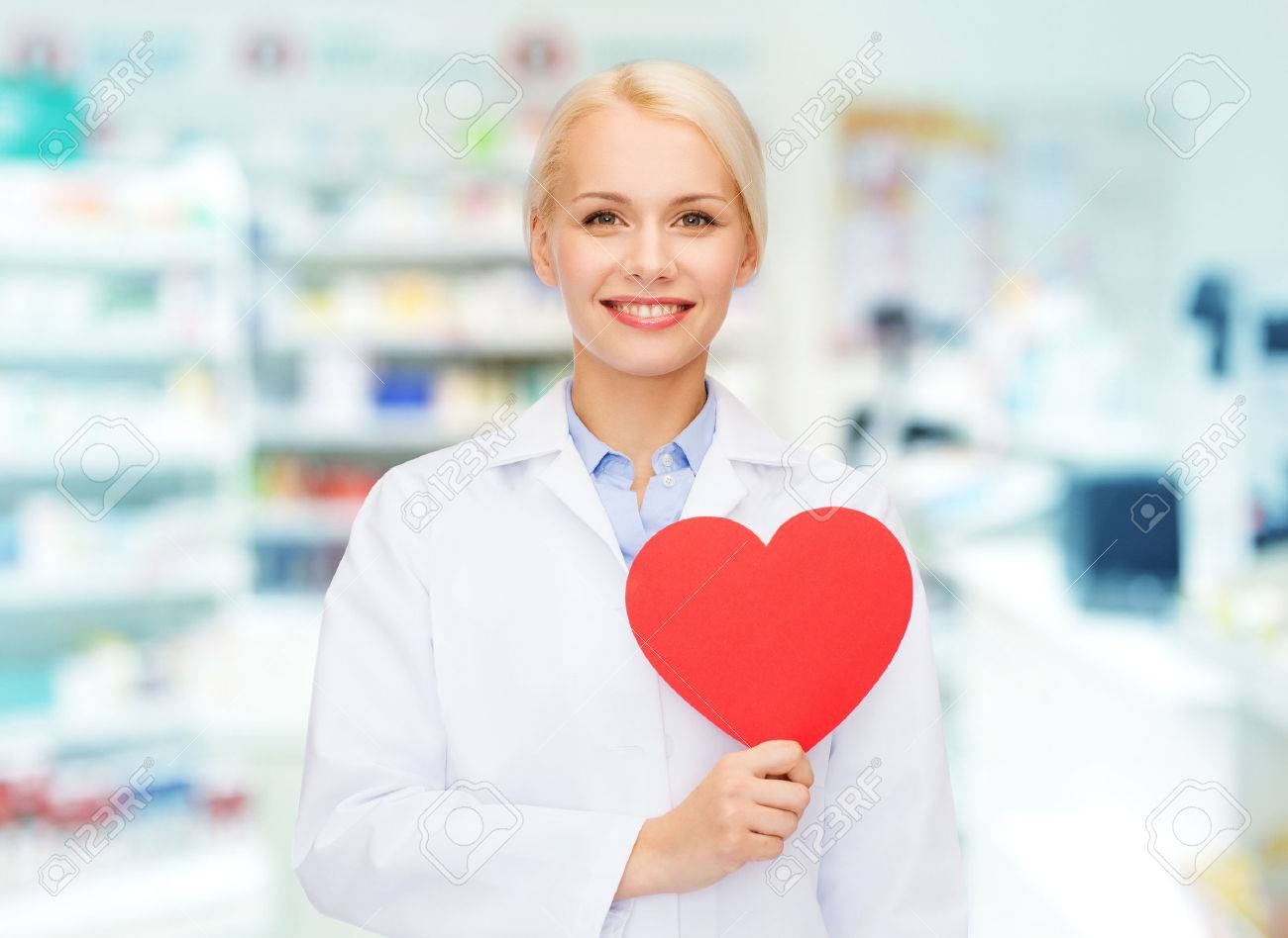 medicine, pharmacy, people, health care and pharmacology concept - happy young woman pharmacist holding red heart shape over drugstore background - 54787780