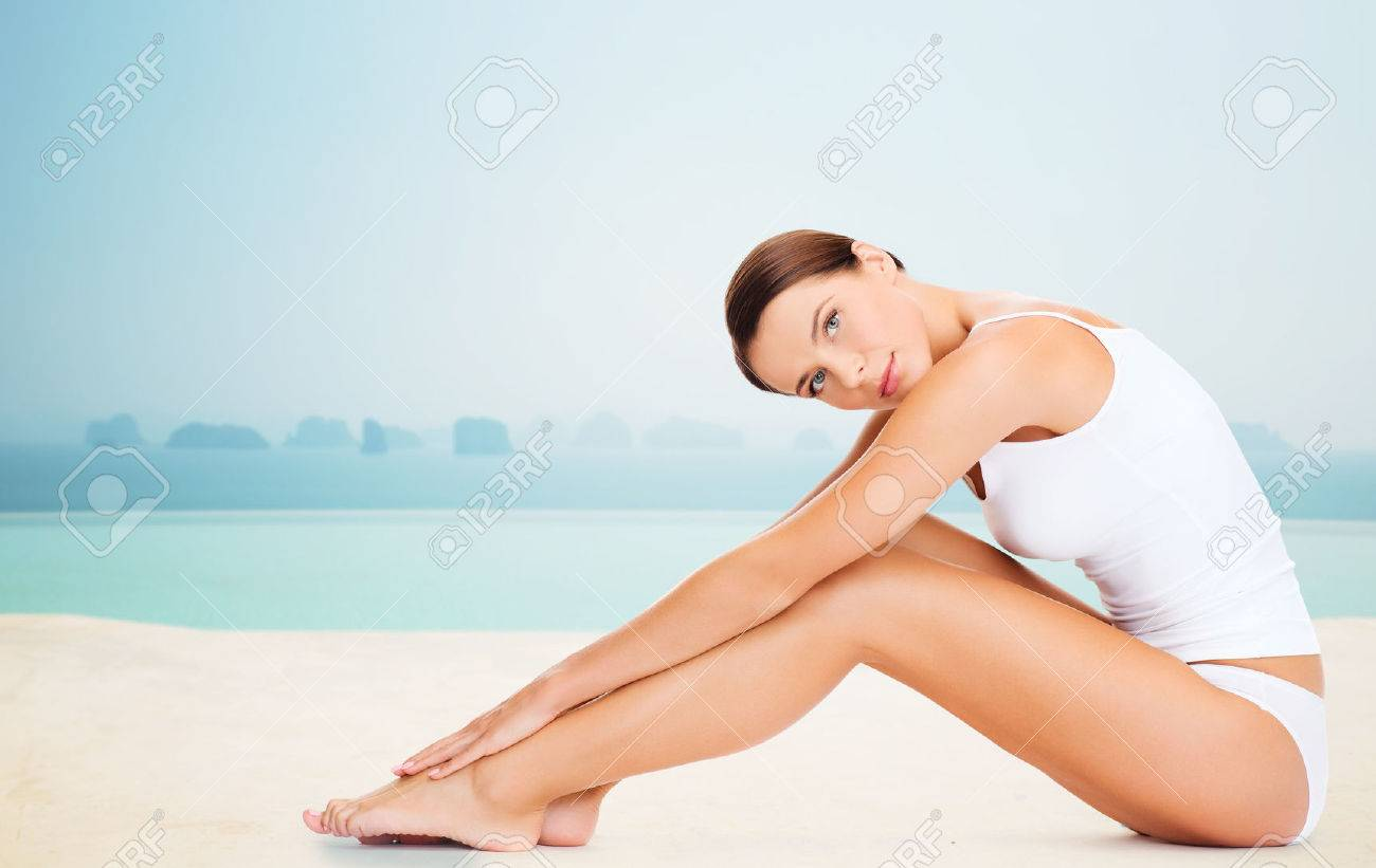 people, beauty, spa and resort concept - beautiful woman in cotton underwear touching her legs over infinity edge pool background Stock Photo - 54788112