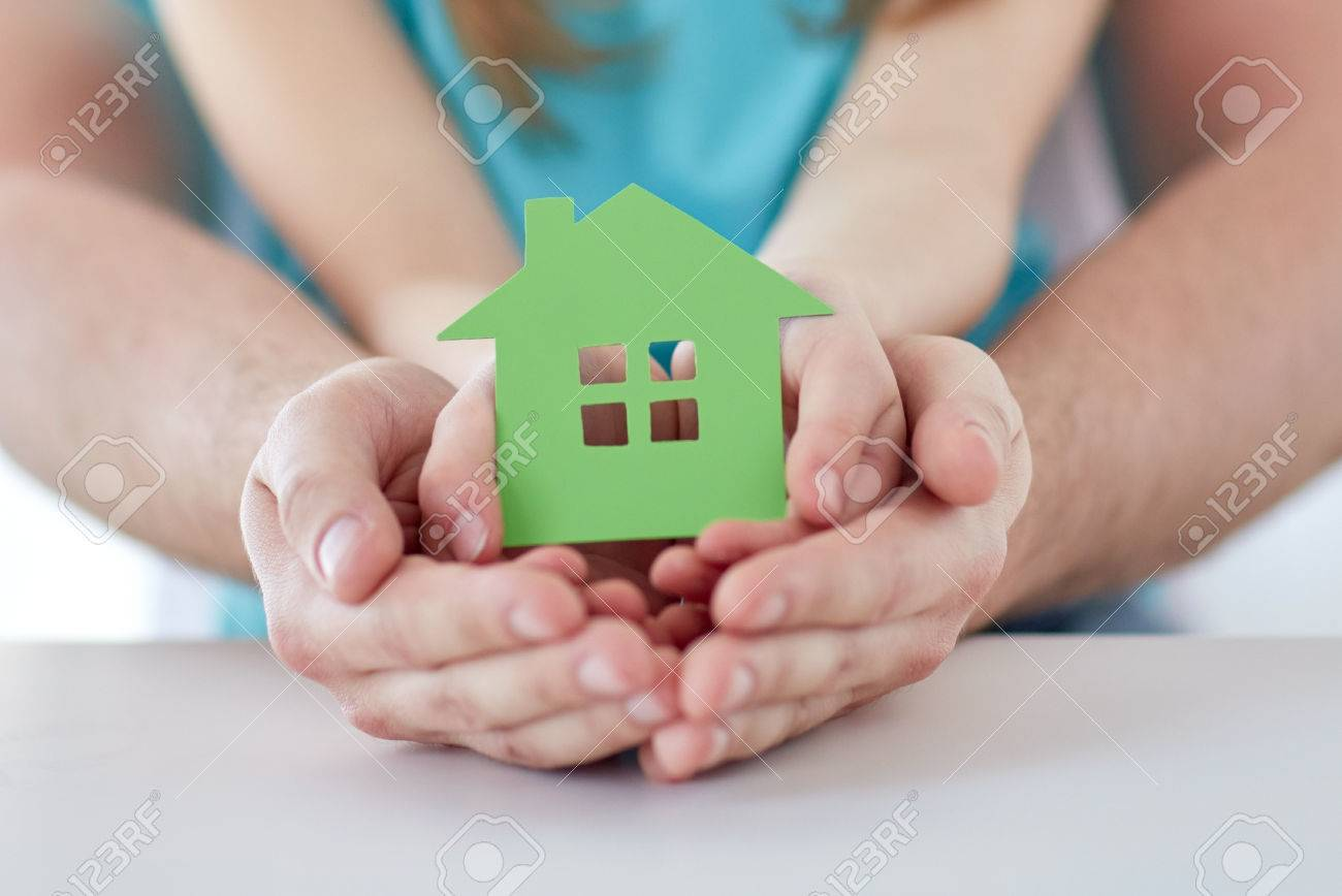 people, charity, family, real estate and home concept - close up of man and girl holding green paper house cutout in cupped hands - 57275914