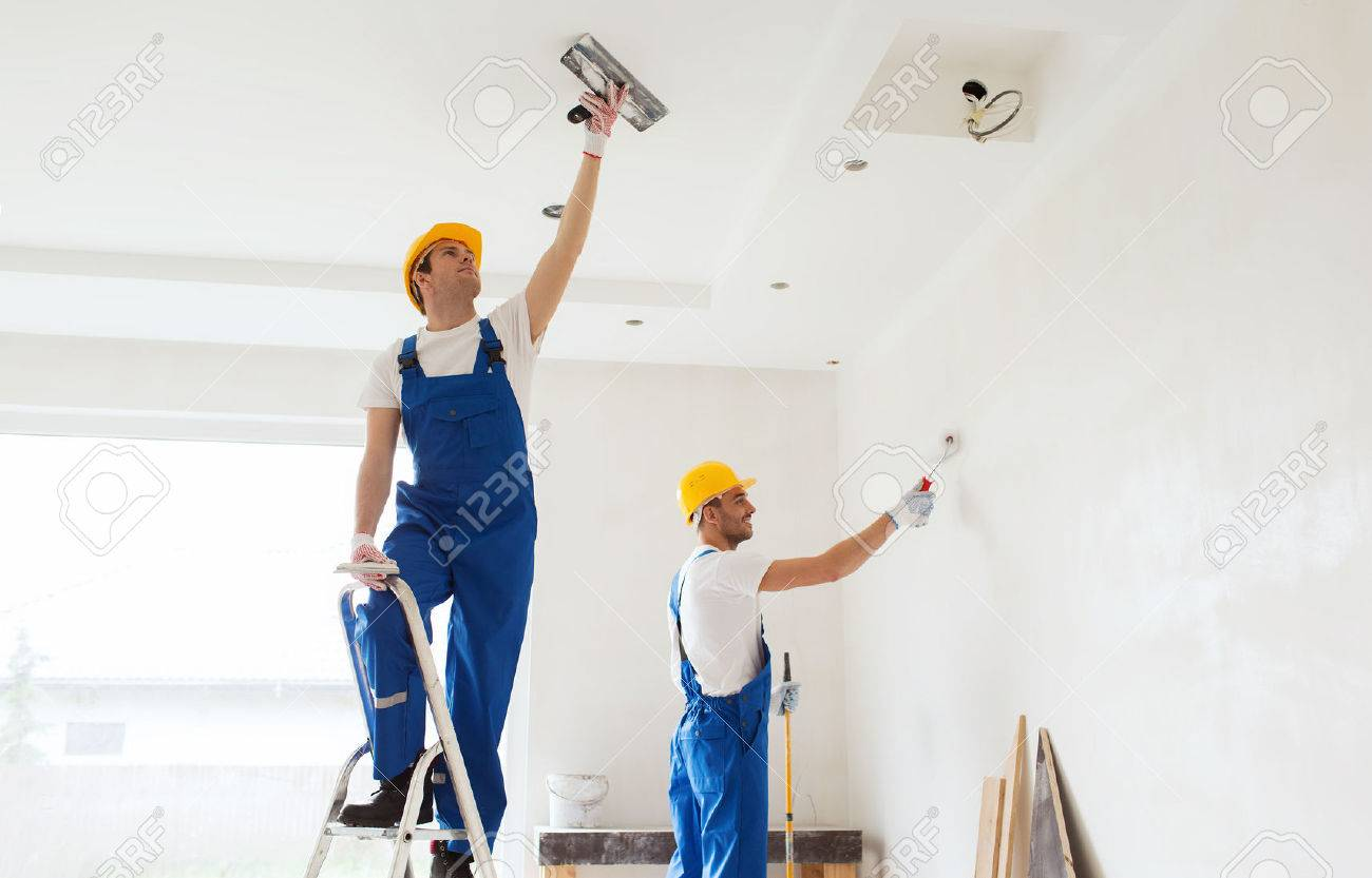 business, building, teamwork and people concept - group of builders in hardhats with plastering tools indoors - 57374367