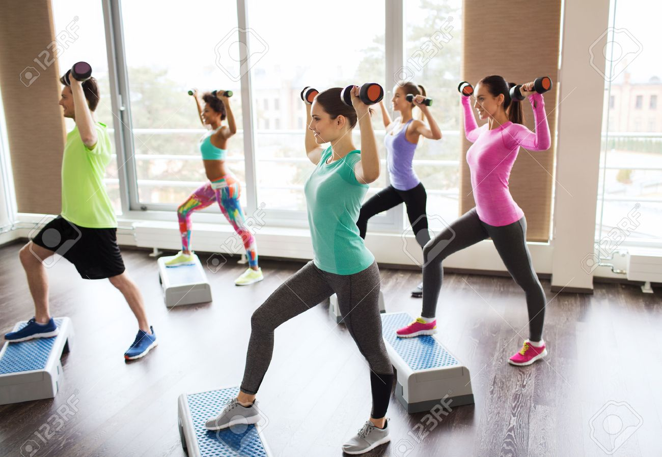 fitness, sport, aerobics and people concept - group of smiling people working out with dumbbells flexing muscles on step platforms in gym - 57374799