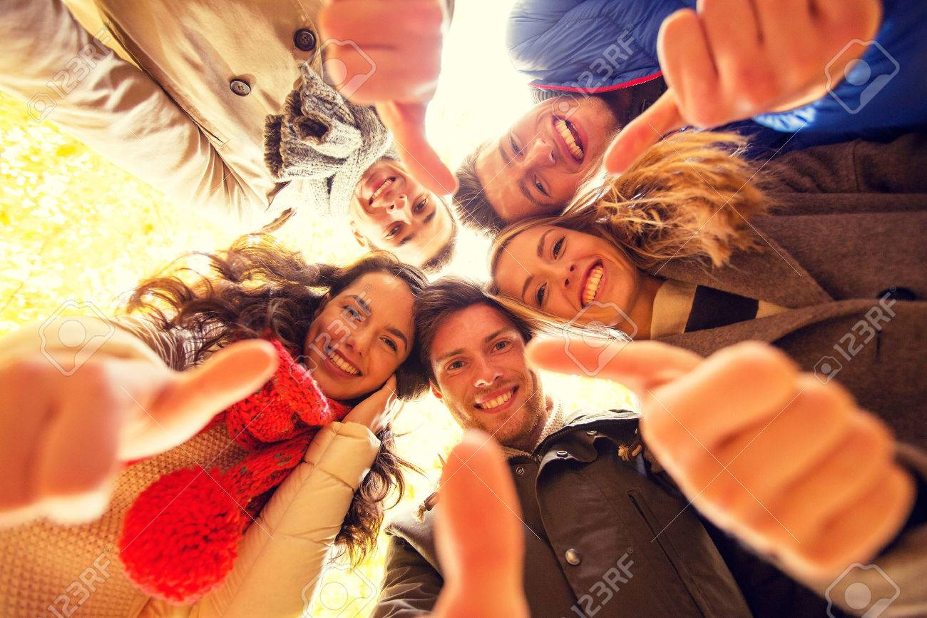 love, friendship, gesture, season and people concept - group of smiling men and women showing thums up in autumn park - 57386433