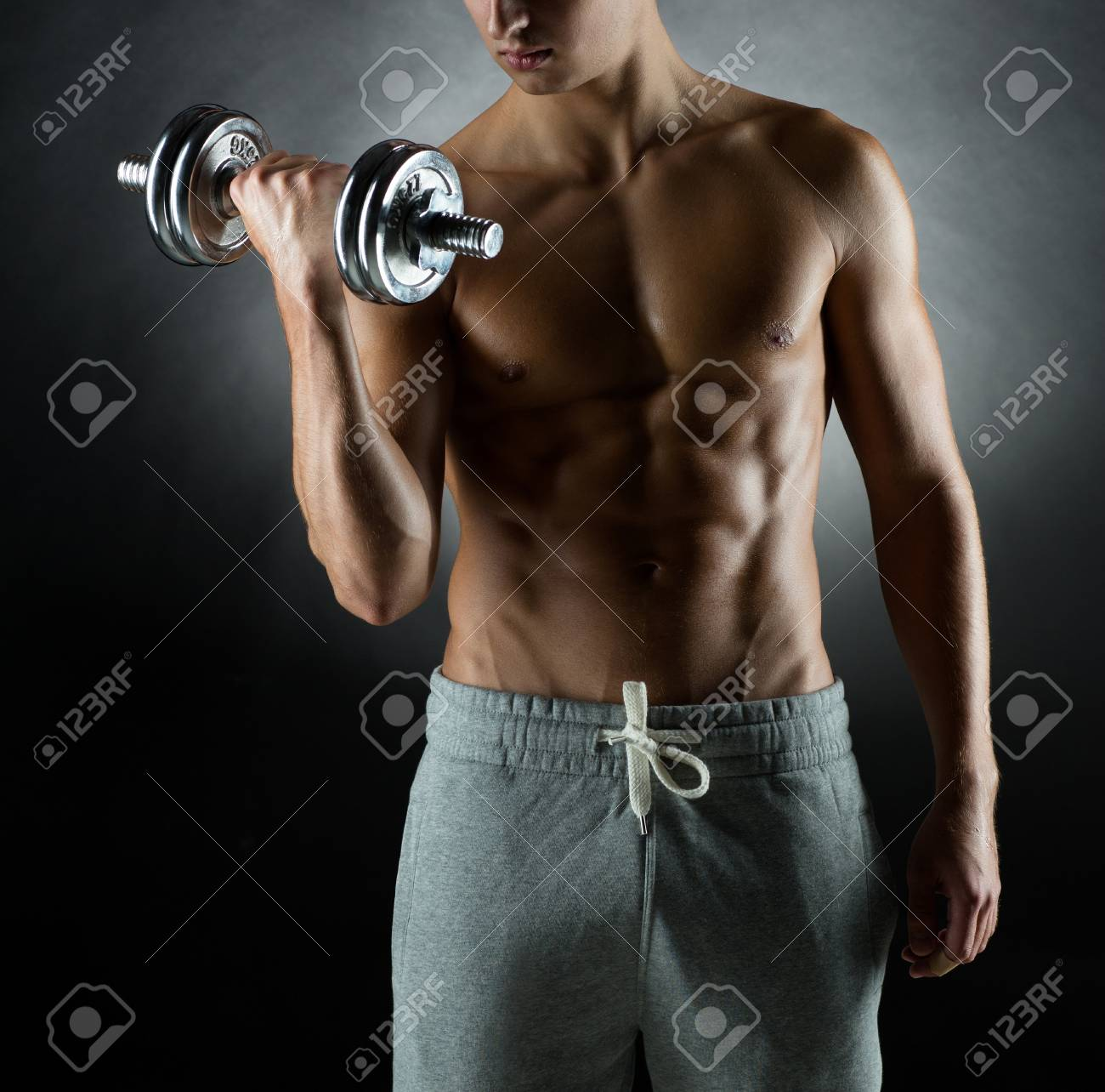 sport, bodybuilding, training and people concept - young man with dumbbell flexing muscles over gray background Stock Photo - 57632299