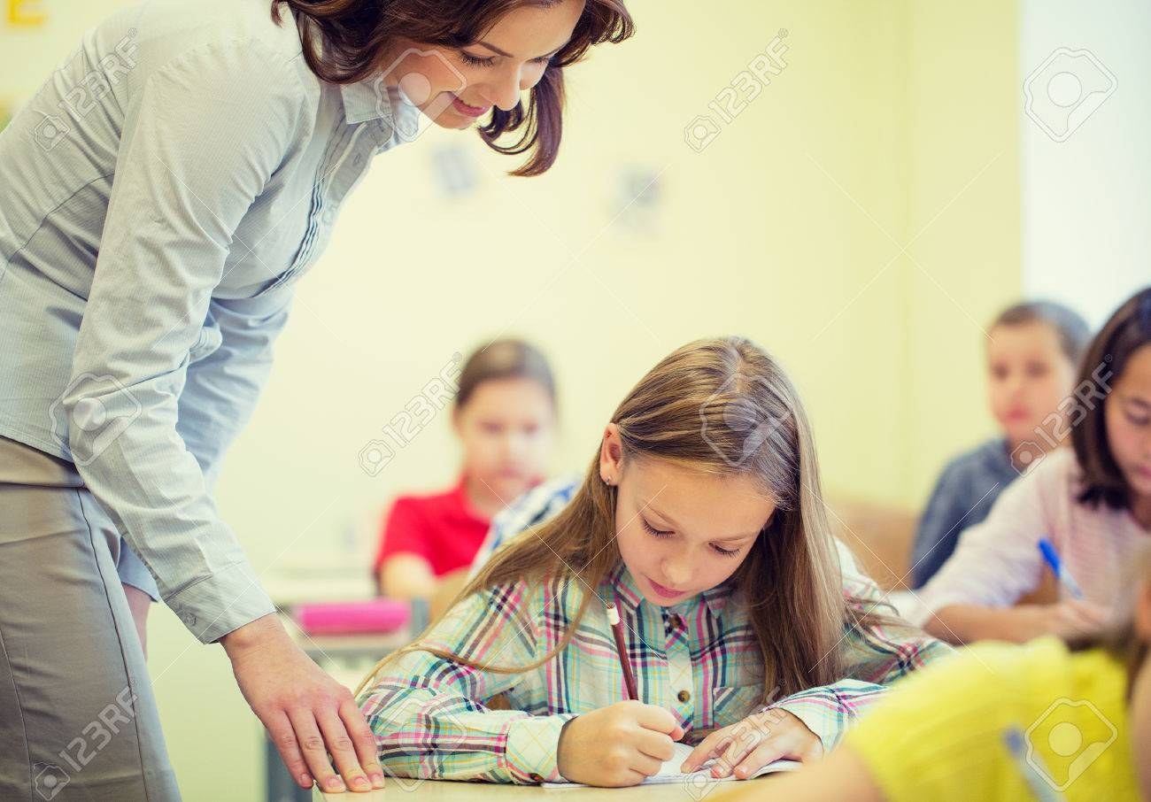 education, elementary school, learning and people concept - teacher helping school girl writing test in classroom - 57631824