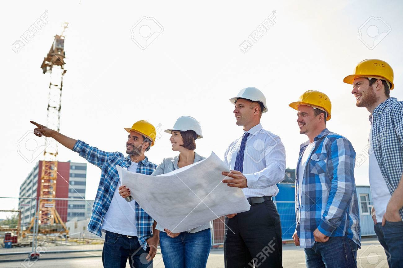 group of builders and architects in hardhats with blueprint on construction site - 57668070
