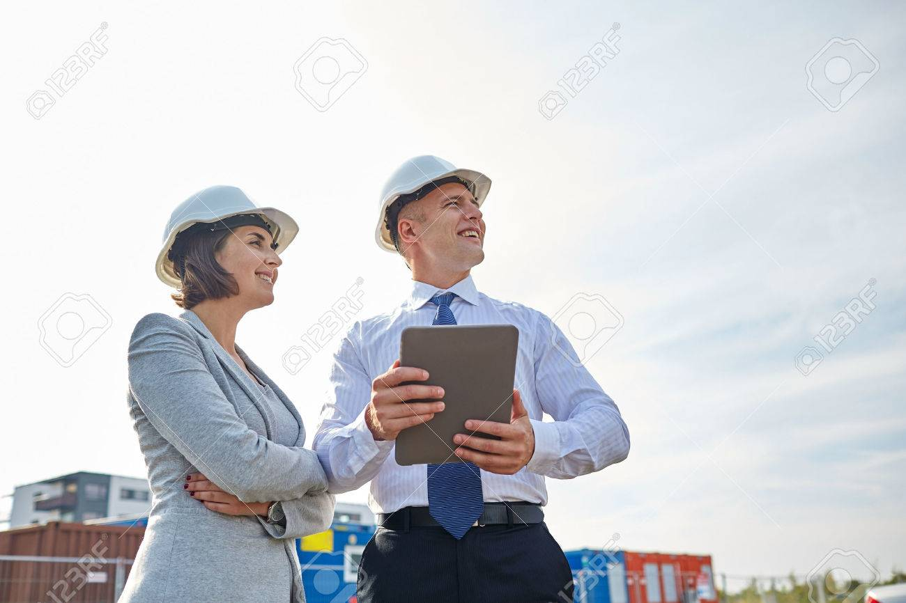 smiling man and woman in hardhats with tablet pc computer at construction site - 57668069