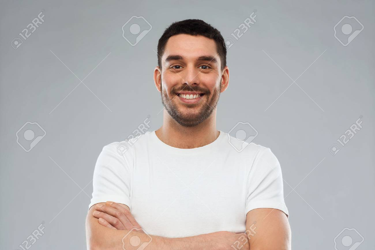 emotion and people concept - happy smiling young man with crossed arms over gray background - 58527631