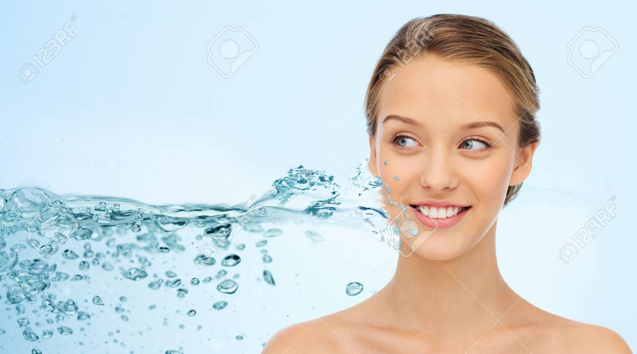 beauty, people and health concept - smiling young woman face and shoulders over water splash and blue background - 58526770