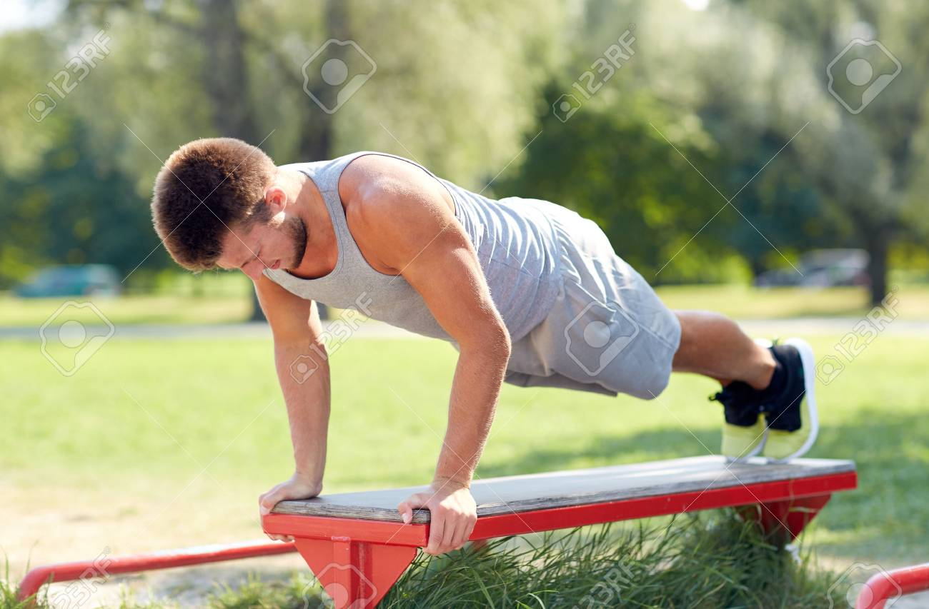 fitness, sport, exercising, training and lifestyle concept - young man doing push ups on bench at summer park - 59328574