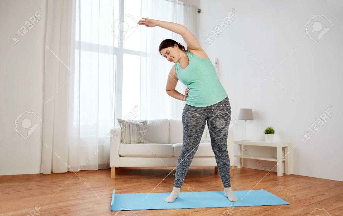 fitness, sport, exercising, training and lifestyle concept - smiling plus size woman stretching on mat at home - 59632682