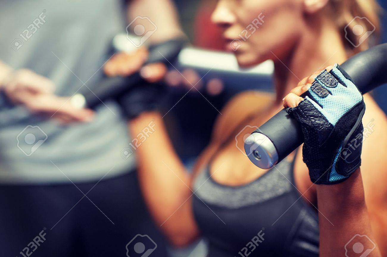 sport, fitness, bodybuilding, teamwork and people concept - young woman and personal trainer flexing muscles on gym machine - 60086756