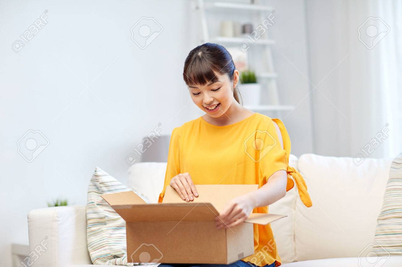 people, delivery, commerce, shipping and shopping concept - happy asian young woman with cardboard parcel box at home - 60348889