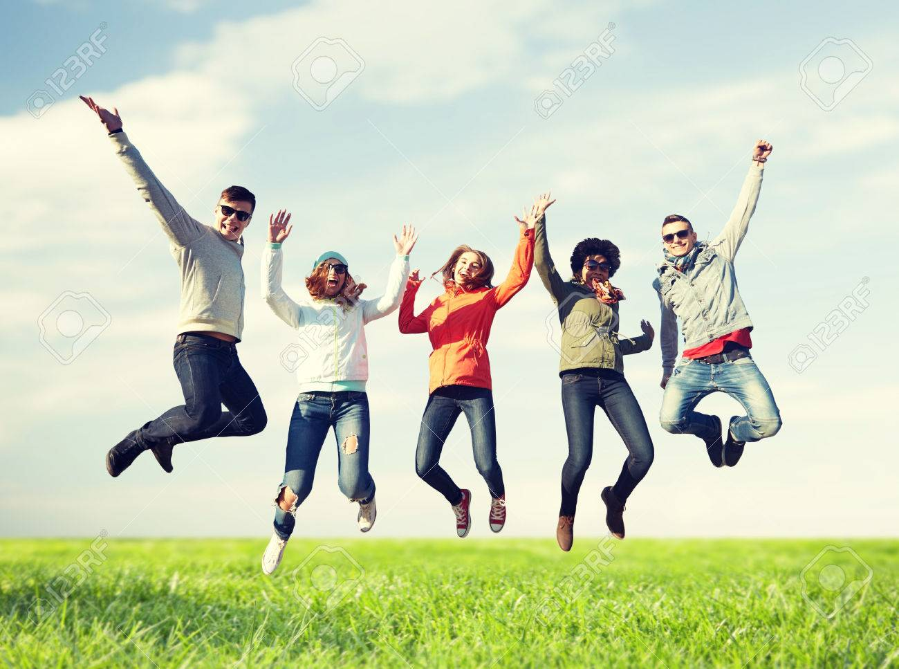 people, freedom, happiness and teenage concept - group of happy friends in sunglasses jumping high over blue sky and grass background - 61136560