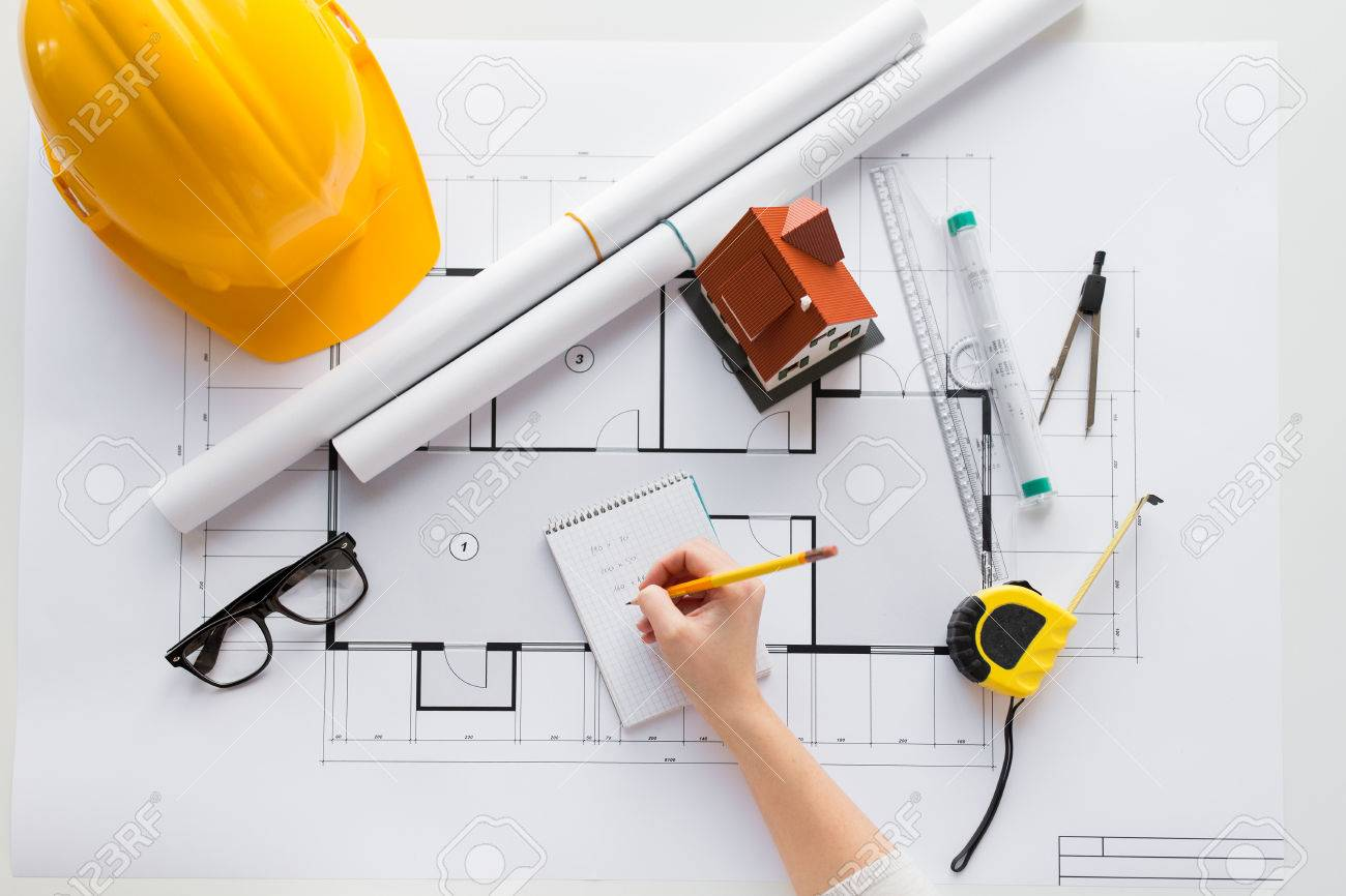 business, architecture, building, construction and people concept - close up of architect hand with blueprint and architectural tools writing to notebook - 61180748