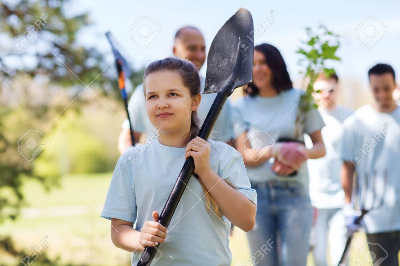 volunteering, charity, people and ecology concept - group of happy volunteers with tree seedlings and rake walking in park - 62354054