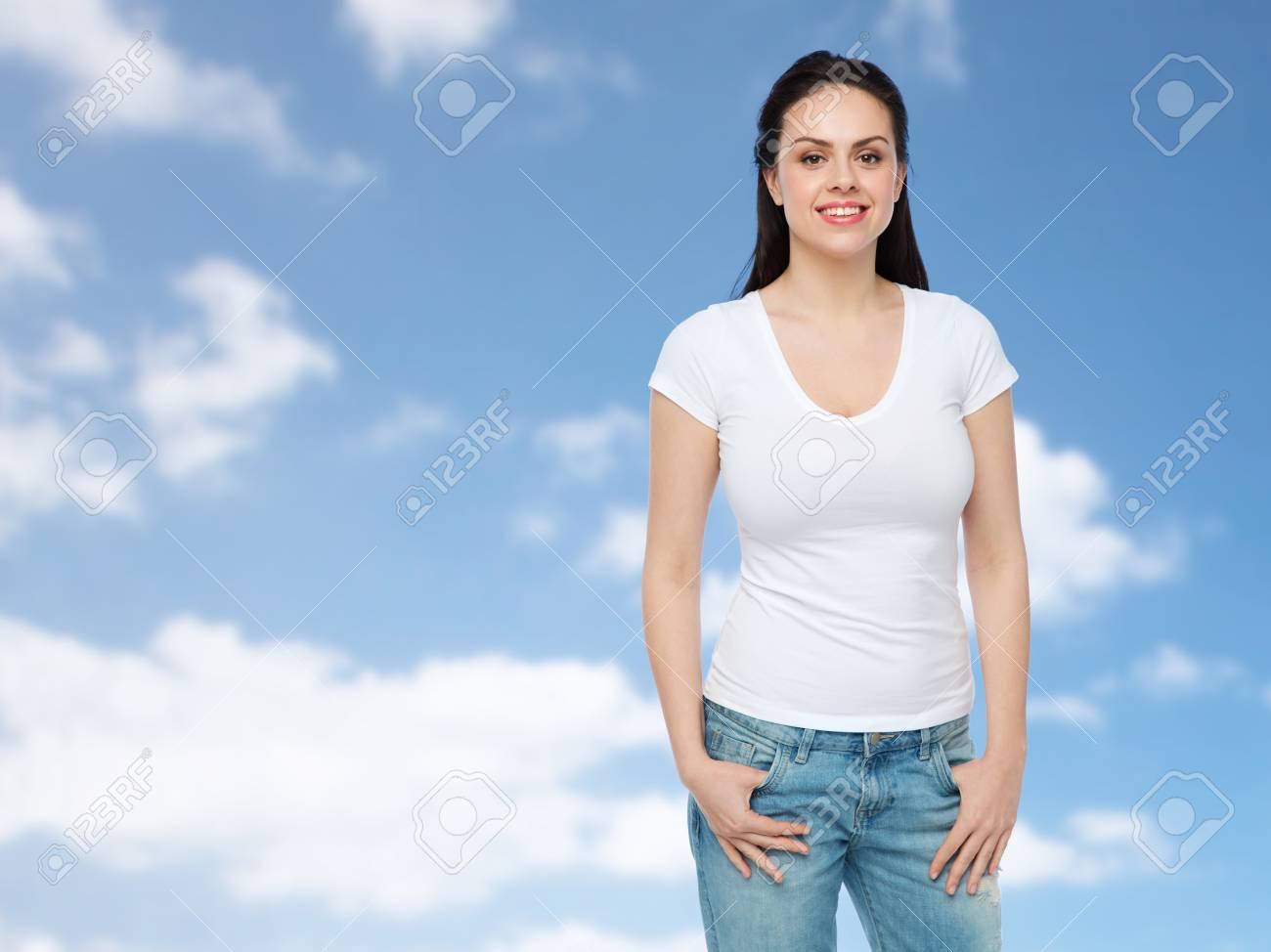 werbung, kleidung und menschen konzept - glückliche junge frau oder  teenager-mädchen in weißen t-shirt über blauen himmel und wolken  hintergrund
