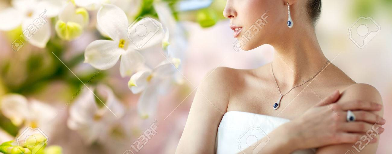 beauty, jewelry, people and luxury concept - beautiful asian woman or bride with earring, finger ring and pendant over natural spring lilac blossom background - 62562236